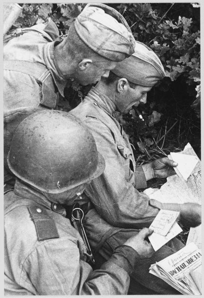 Soviet soldiers receive mail and newspapers at the front