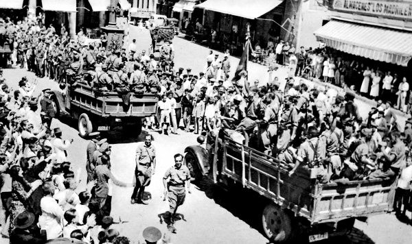 Photograph showing lorries full of the Nationalist Spanish Foreign Legion passing through a town in Andalucia, Southern Spain, on the way to the Madrid front, 1936