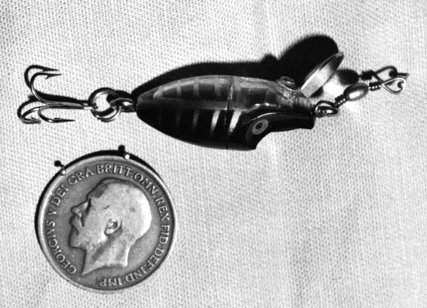 A 'Mity Mijit'spinner (spinning fishing lure), photographed beside a King George V coin to show how miniscule it is. Date: 1960s