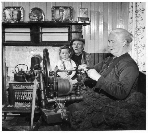 Production of Harris Tweed. A typical scene in an island home as the crofter spins her yarn