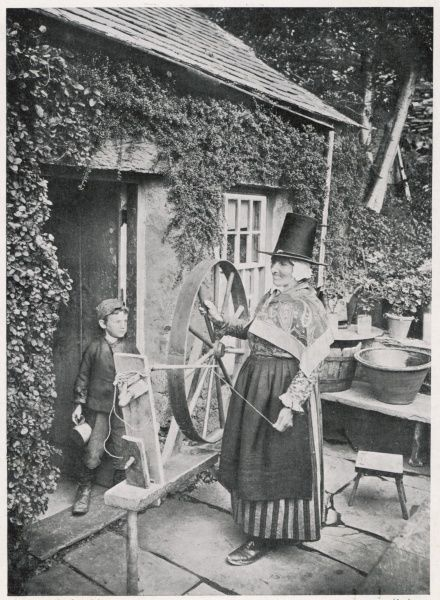 A Welshwoman in traditional dress poses rather self- consciously outside her cottage with a spinning wheel