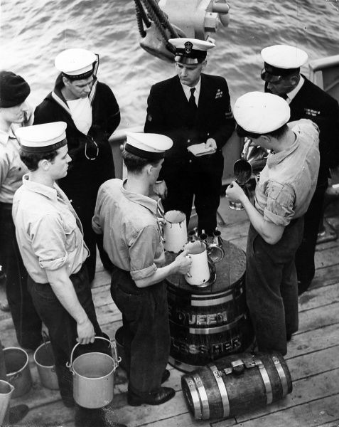 Photograph showing the distribution of rum to ratings on board HMS 'Cleopatra' after Queen Elizabeth II's first order - 'splice the mainbrace' - following her review of the fleet