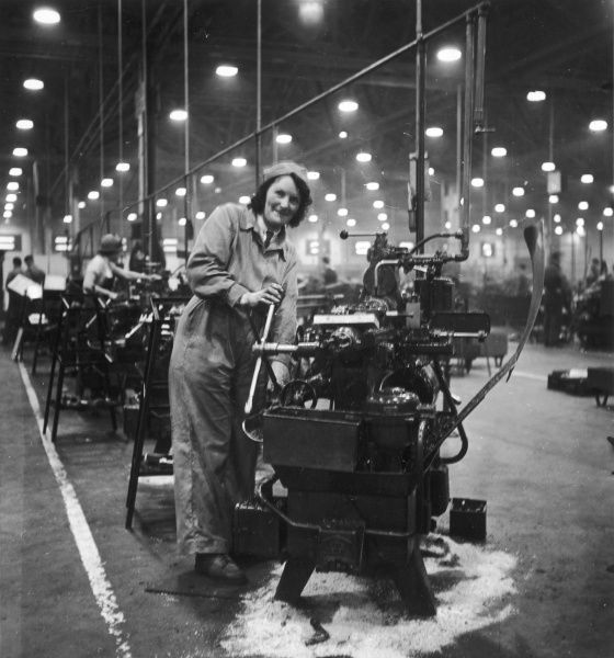 A woman making Spitfire parts on her machine in a Spitfire aircraft factory during World War II