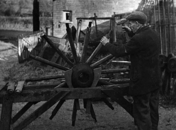A wheelwright fitting spokes to the hub of a wheel, Berkshire, England. Date: 1930s