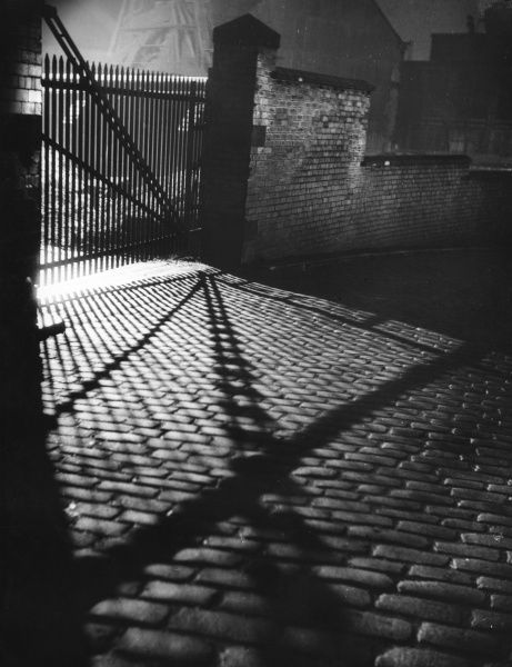 Spooky shadow patterns from an iron gate across a cobbled street... Date: 1930s