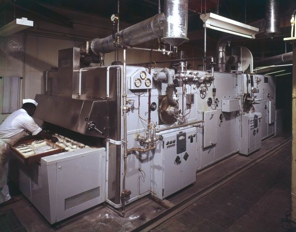An immense Spooner Travelling Oven - with baked loaves of white bread being placed inside the large central baking oven, before moving through the next stage of the process via a peripheral system of rollers and conveyor belts