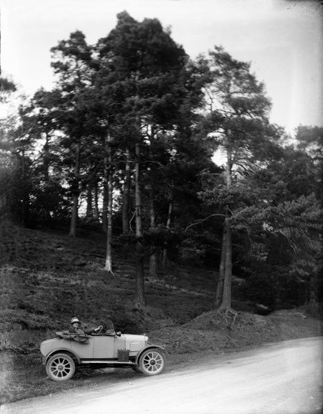 Sports car parked at the roadside below a tree-clad embankment - the lady driver looks across the road toward the cameraman