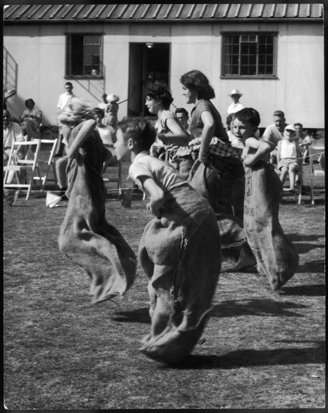 Boys and girls of various ages race against one another in the sack race