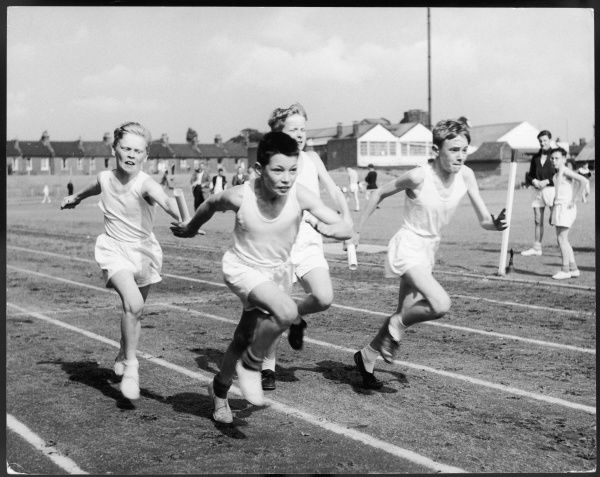 Four very determined-looking boys take part in a sprint relay race at a school sports day