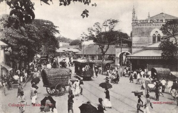 Sri Lanka - Colombo - The busy Main Street with a tram, rickshaws and a host of pedestrians getting on with their lives. Date: circa 1920