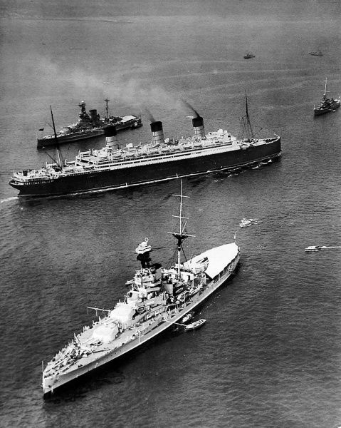 Photograph of the Cunard Liner SS 'Berengaria' passing through the lines of the British Fleet, assembled for the Spithead Review, on her homeward journey from New York. The 'Berengaria', built in 1912 for the Hamburg-American Line