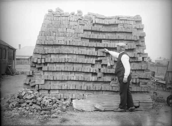 An old man stacking bricks in an industrial brick yard. Date: early 1930s