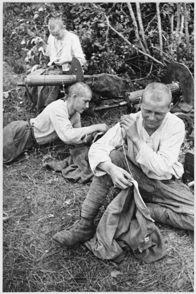 Soviet troops rest behind the front line and make repairs to their uniforms