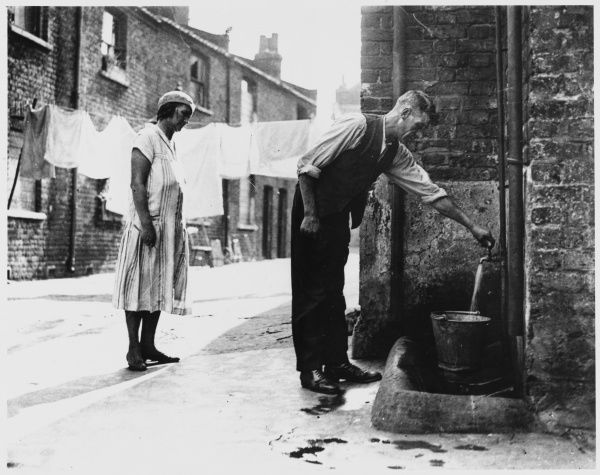 A man fills a bucket from a public standpipe in an urban street