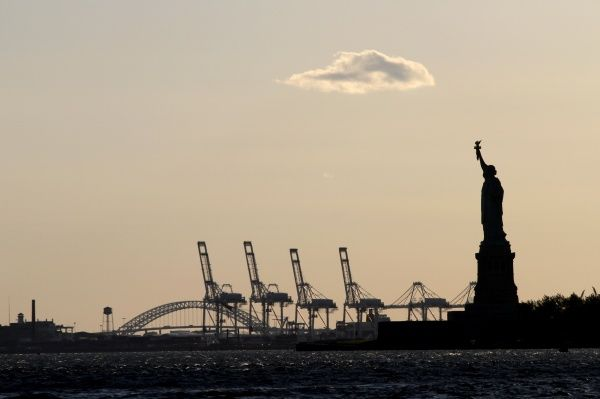 The Statue of Liberty and cranes at the docks silhouette in New York, America circa 2008