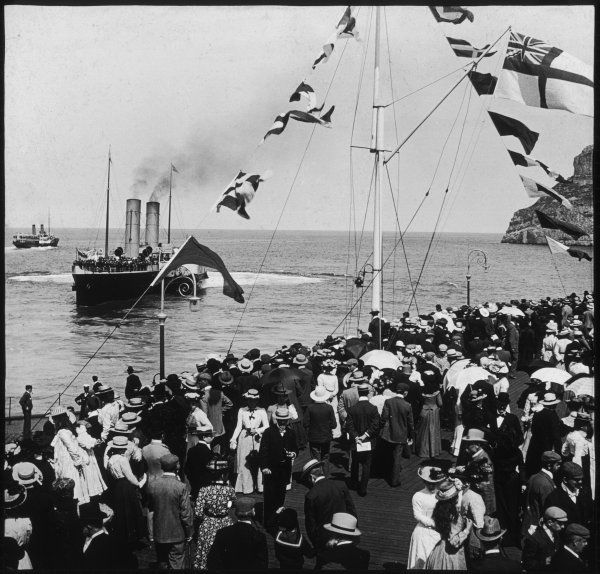 A crowd clamour to get a good glimpse of 'St. Elvies' a paddle steamer of the Liverpool and North Wales Steamship Co., at Llandudno, North Wales