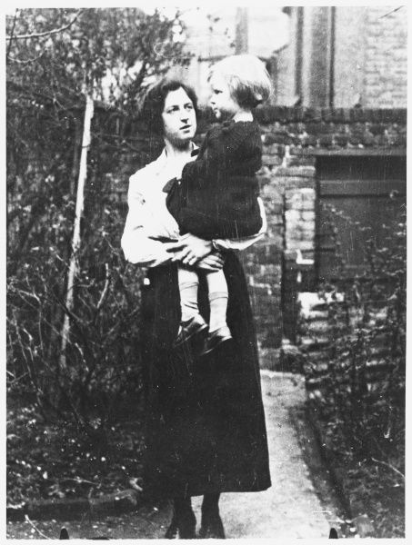 Full length portrait of Stella Cranshawe, spirit medium, holding a child in her arms