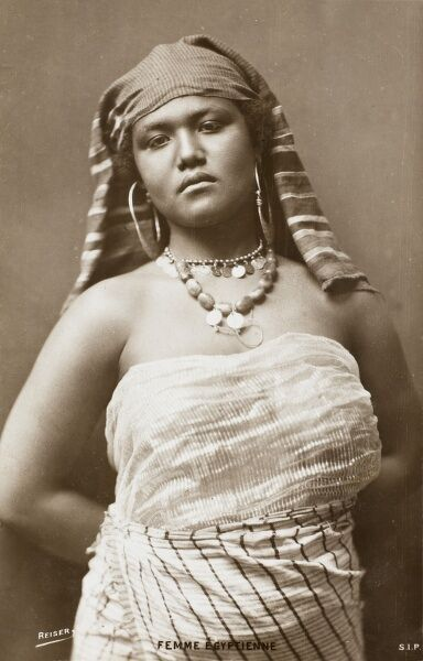 The original model with attitude! A stern-faced Egyptian girl stands with her arms behind her back, wearing headscarf, necklace and immense hooped metallic earrings and a thin, revealing dress