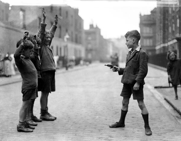 'Stick 'em up'! Boys playing with guns on the street