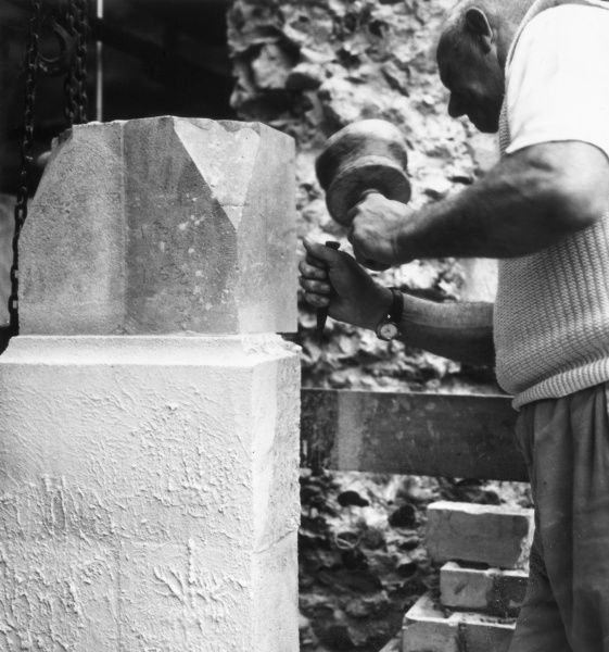 A stonemason at work, sculpting a stone slab with his mallet and chisel, south east England. Date: 1960s