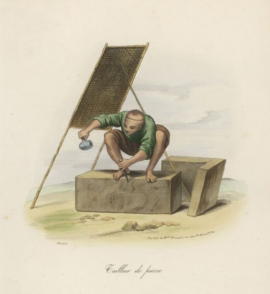 A Stonemason prepares a large block of stone whilst sheltering from the hot sun below a wicker shade