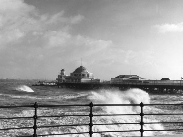 Stormy weather and waves crashing against the pier at New Brighton, Cheshire, England. Date: 1960s