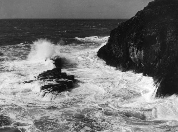 Waves crashing against the rugged cliffs at Tintagel, Cornwall, England. Date: 1930s
