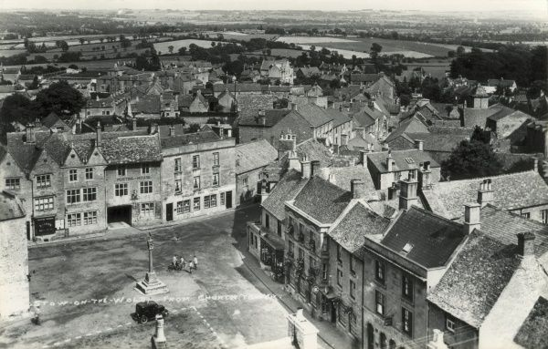 A bird's eye view of Stow on the Wold, Gloucestershire, from a church tower. A single car stands in the square below. Towards the top left of the picture, the now demolished Stow on the Wold workhouse can be seen. The building, erected in 1836
