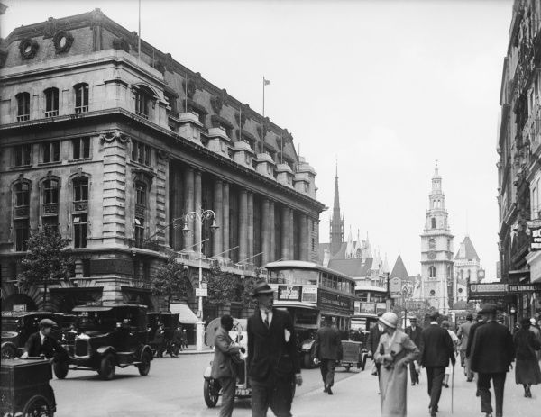 A busy scene on The Strand, showing businessmen bustling about and Australia House across the street