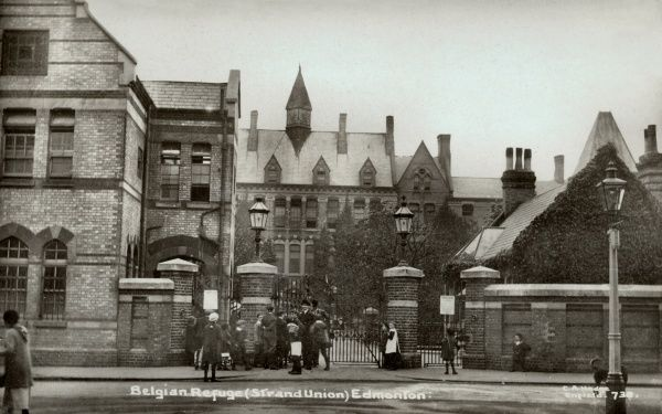 The Strand Union Workhouse at Edmonton used to house Belgian refugees during the First World War. A group of adults and children, some carrying parcels, are milling around the entrance gates. Date: circa 1915