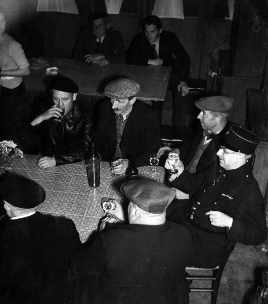 Men doing a spot of Sunday wine-tasting in their local cafe, an unusual change from their normal beer drinking; Strasbourg, France. Date: 1930s
