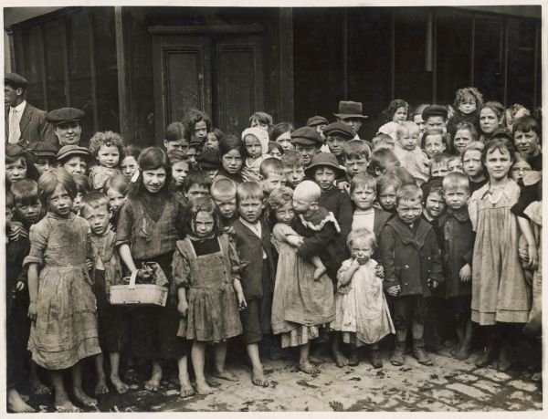 A gathering of street boys and girls: many of them are barefoot on the stone cobbles