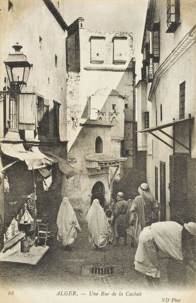 Looking down a street in the Kasbah, Algiers, Algeria. Some of the upper levels of the houses have ornate bird houses. The European influence in the city is clearly marked by the ironwork lamp (left)