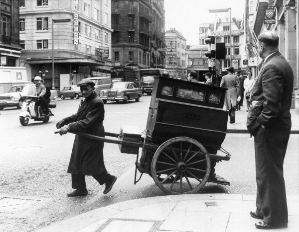 An organ grinder pulls his barrel organ along a London street. Date