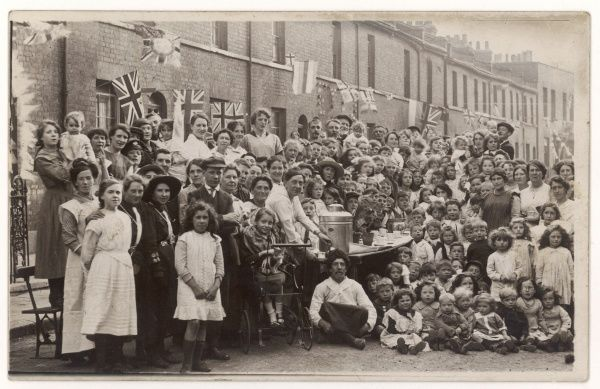 A large crowd of people taking part in a street party for the Coronation of King George V. The location is Acland Street, Limehouse, London E14