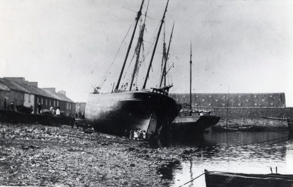 View of Front Street and Pembroke Dock, Pembrokeshire, South Wales. A group of children stand near the prow of a large ship, moored on the shingle