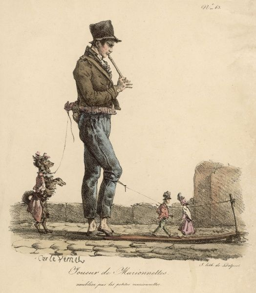 A street musician with dancing dog and two small marionette puppets attached between a peg and his knee