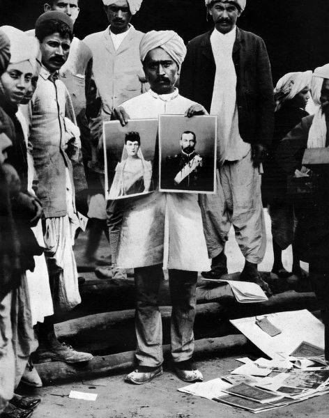 A street vendor in Delhi doing a roaring trade selling portraits of King George V and Queen Mary during the Durbar period in December 1911. Date: 1911