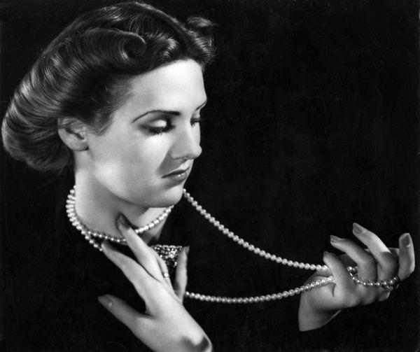 A stylish woman shows of her pearl necklace. Date: 1940s