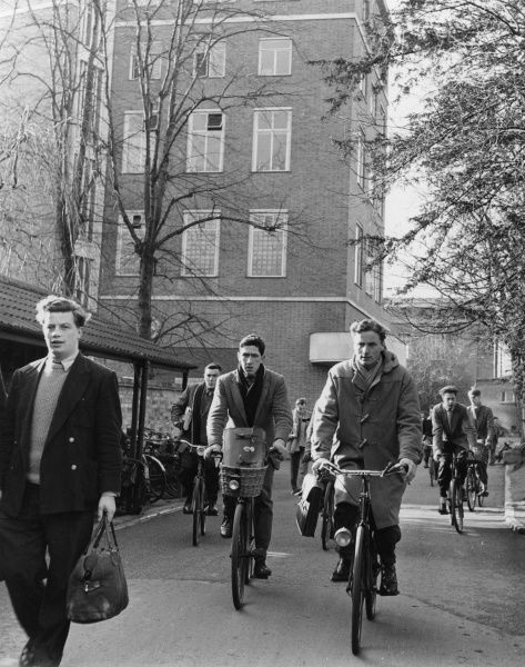 Young male students leaving the engineering building at Cambridge University, many on bicycles Date: circa 1960
