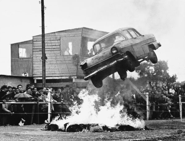 A stunt car flies through the air over a bonfire of tyres and the crowd, standing in the rain, are loving it! Date: 1960s
