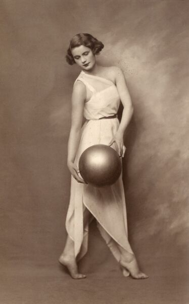 A fantastically stylish and well-compossed photograph of a young lady in a delicate white dress, posing holding a large shiny ball. Date: late 1920s