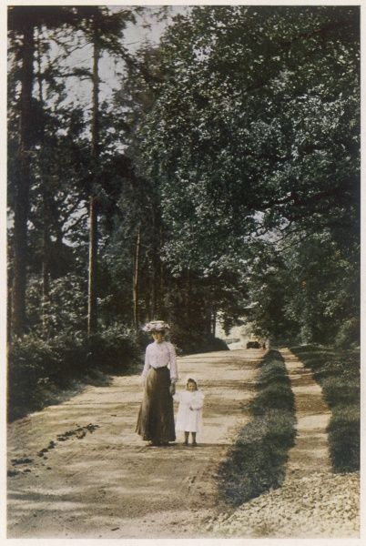 A mother and child walk hand in hand along an English suburban road, unmade-up but with a sidewalk though the pair aren't using it