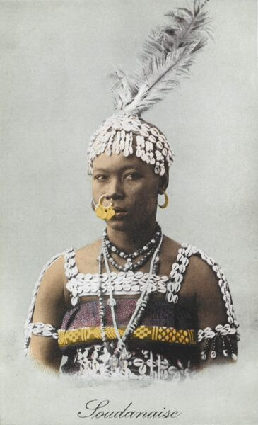 Sudanese Woman, wearing a fantastic decorated nosering, headdress made out of small white cowrie (cowry) shells and topped with large feathers. Her dress is also edged with small shells and beads