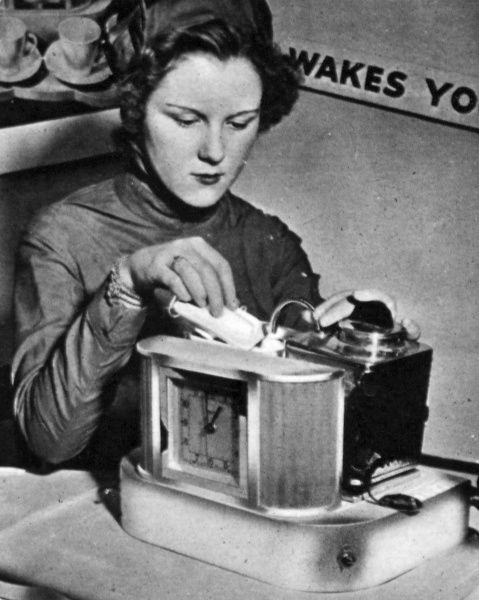 Photograph of a woman demonstrating the electric teas-made at the Olympia Ideal Home exhibition 1947