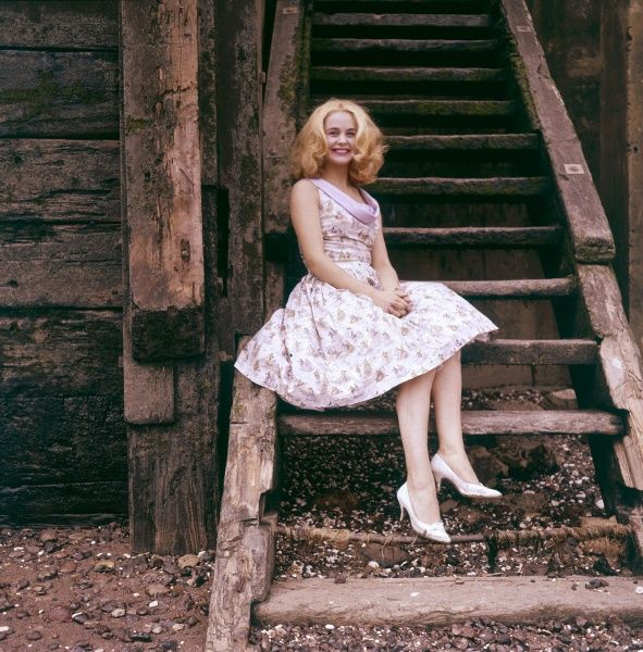 A lovely blonde girl, sitting on some wooden beach steps, wearing a summer dress and white stilettos. Date: circa 1960