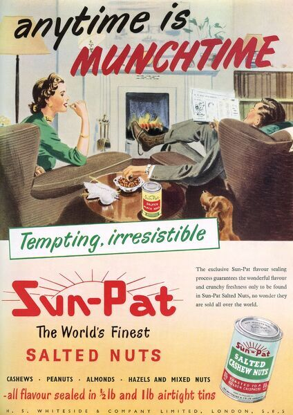 Advertisement for Sun-Pat peanuts depicting a comfortable domestic scene with a couple enjoying Sun-Pat peanuts as they sit in their living room in front of a blazing fire. Date: 1953