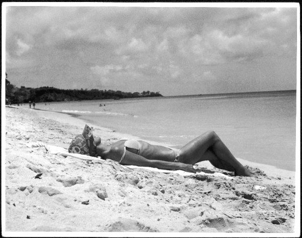 A bronzed woman, in sun hat & white bikini to emphasize her tan, sunbathes on a sandy beach