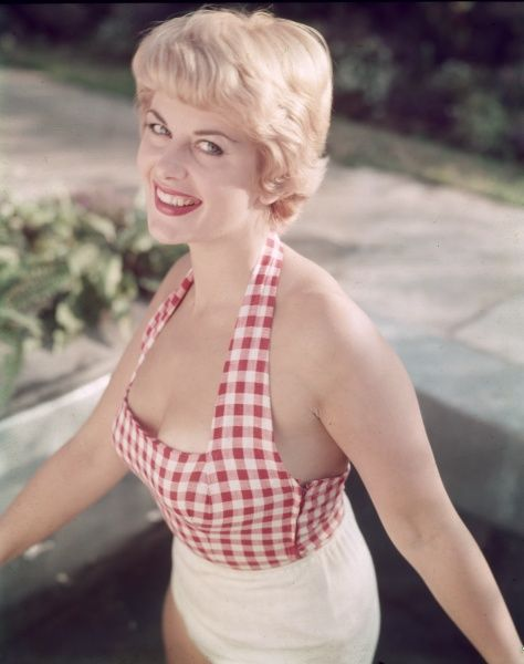 A pretty short-haired blonde model with a sunny smile wears a red gingham halter-neck sun- top & white shorts
