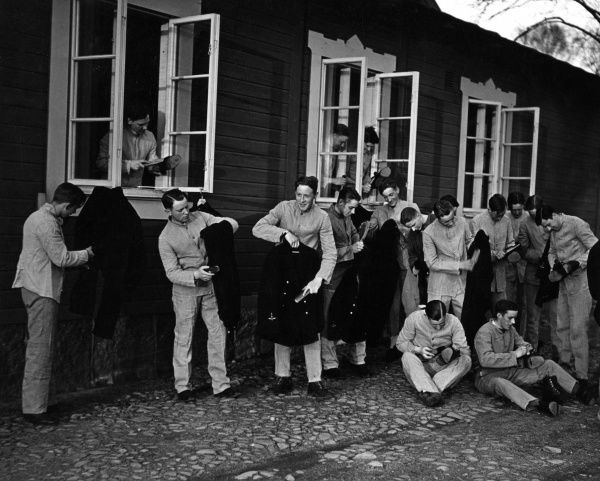 New Swedish Air Force recruits sorting out their uniforms in front of their barracks. Date: 1930s